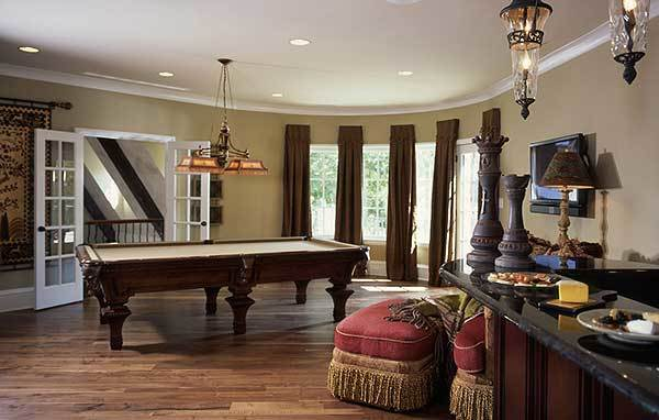 The game room has a billiards table, wet bar, and a bay window dressed in brown draperies.