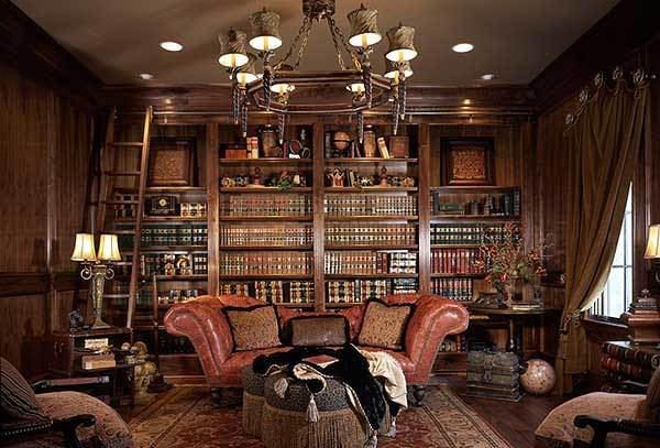 Study with leather sofa, cushioned chairs, oversized chandelier, and a built-in bookcase lined with a ladder.