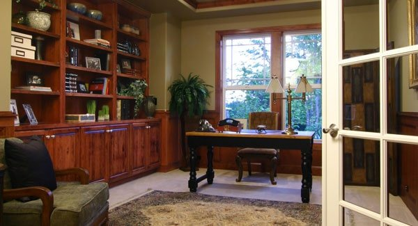 Study with cushioned chairs, a wooden desk, and a built-in bookcase.