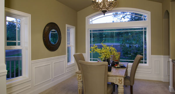 The dining room has a rustic table, high back upholstered chairs, and beige walls adorned with a round mirror and white wainscoting.