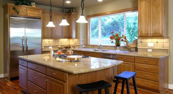 The kitchen is equipped with granite countertops, stainless steel appliances, wooden cabinetry, and a cooktop island.