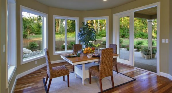 Breakfast nook with wicker chairs, wooden dining table, and a french door that leads out to the covered porch.