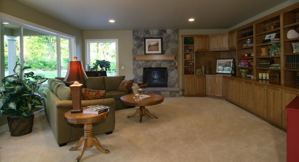 The family room has carpet flooring, a stone fireplace, green sectional, round tables, and a wide wooden built-in.