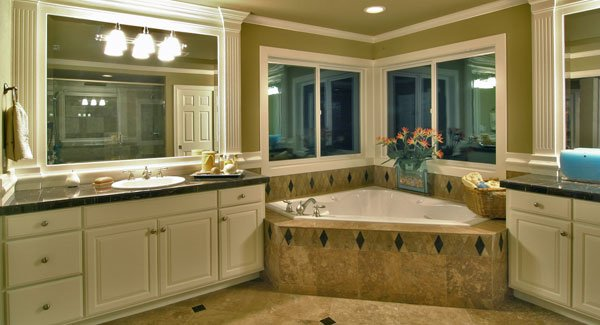 Primary bathroom with his and her vanity along with a corner bathtub fixed under the sliding windows.