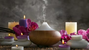 A close look at an aromatherapy oil diffuser, scented candles and flowers.