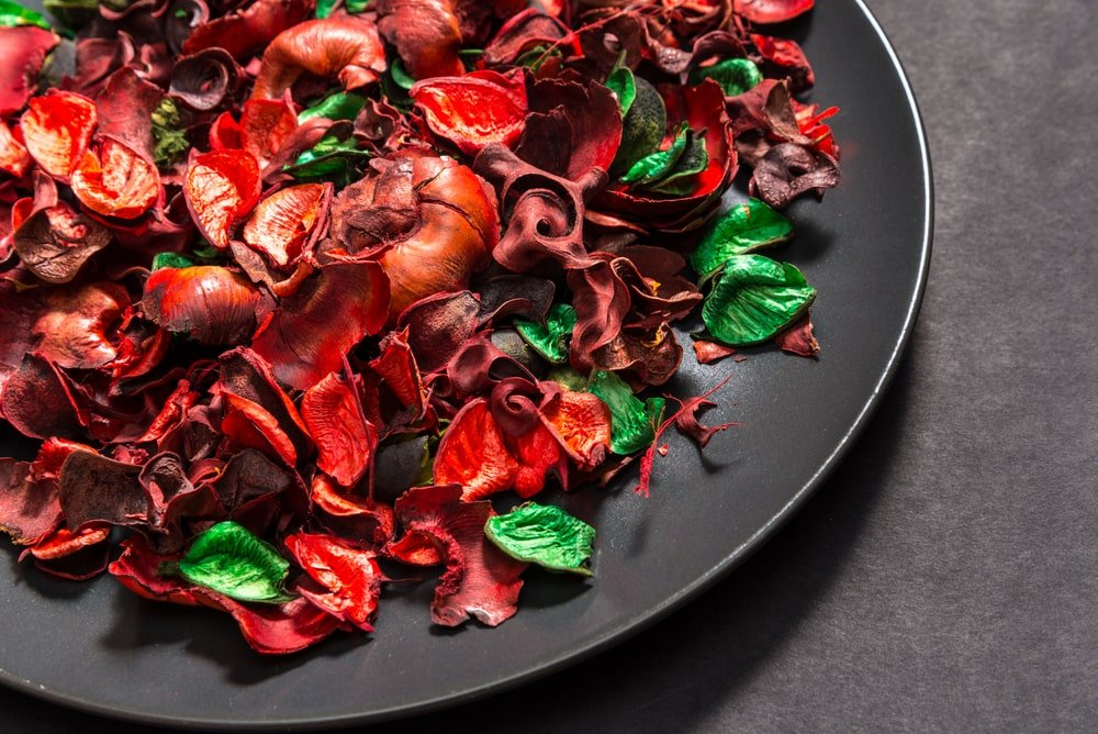 A bunch of potpourri flowers and leaves on a black ceramic plate.