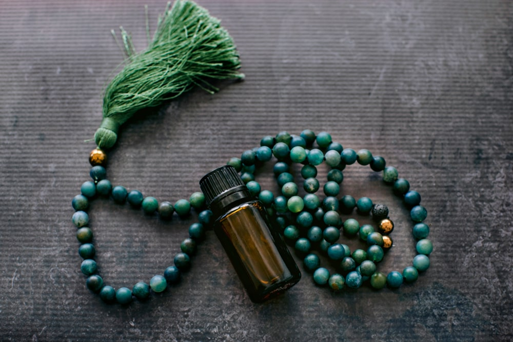 A small bottle of essential oil and jade mala beads on a dark surface.