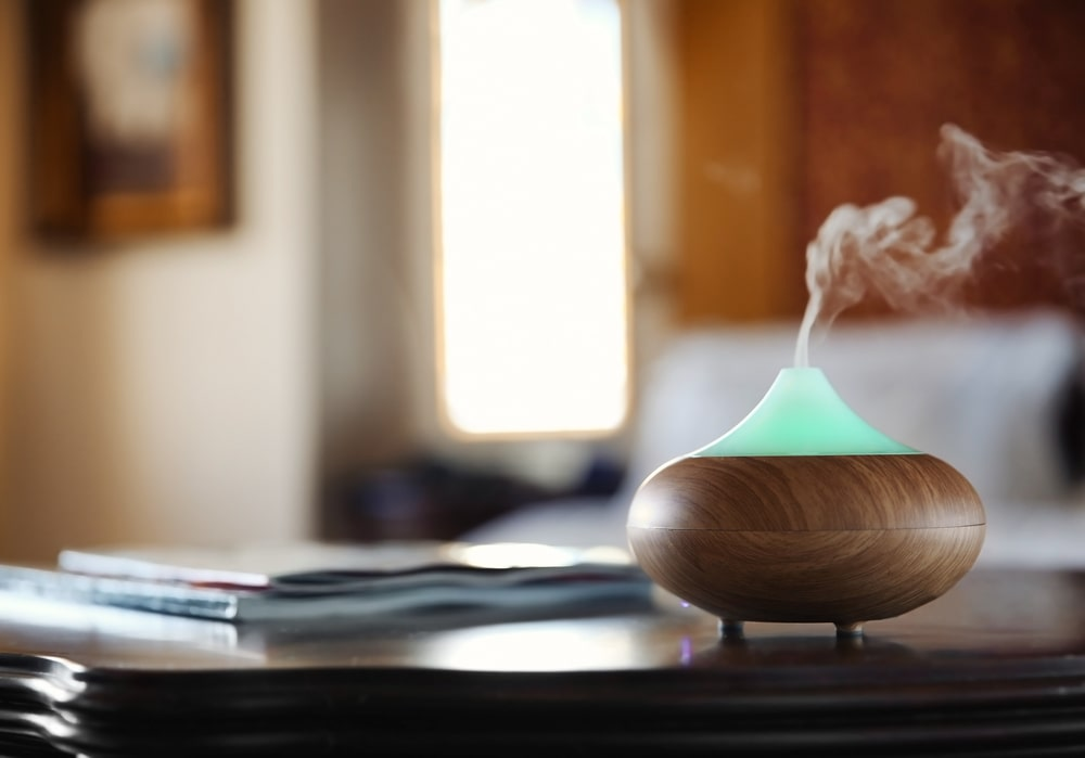 A close look at a non-mechanical aroma oil diffuser on a wooden table.