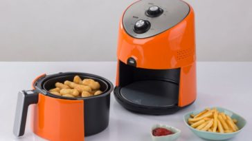 A bright orange air fryer machine with fries and chicken nuggets for samples.