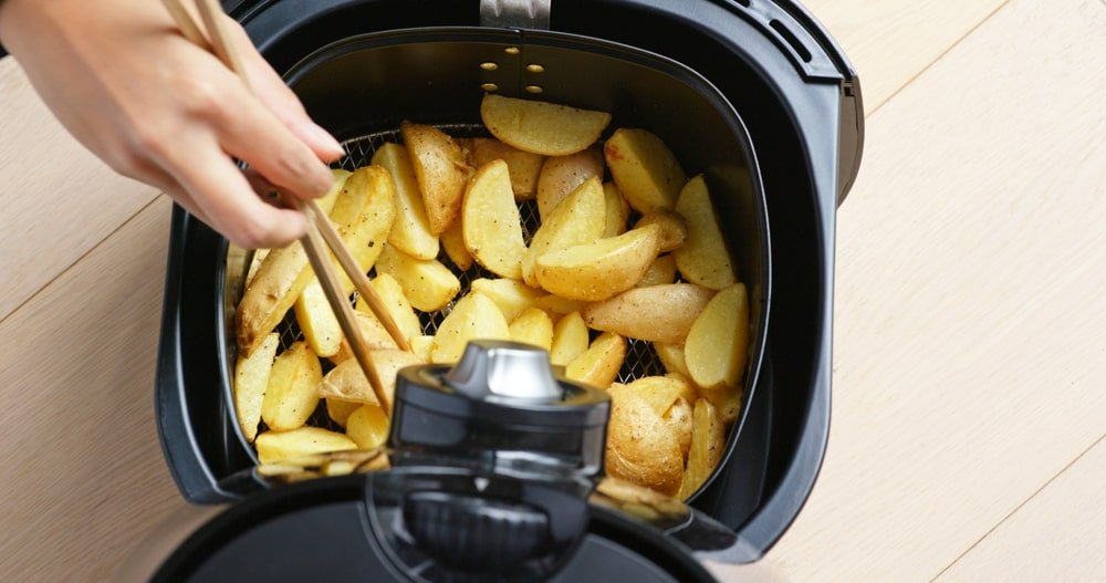A top view of a paddle-type air fryer with crispy potato wedges.