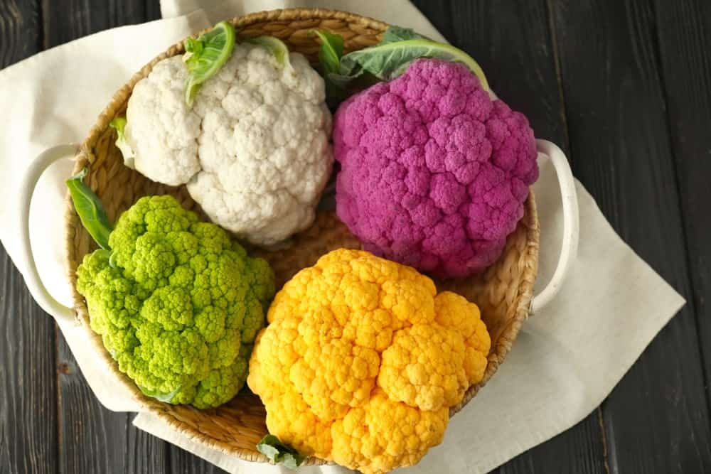Multicolored cauliflowers in a wicker basket.