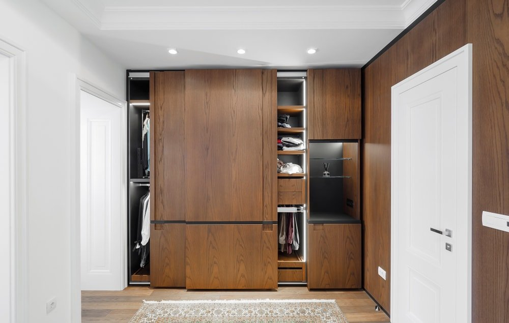 This is a dark wood built-in closet with sliding wooden doors.