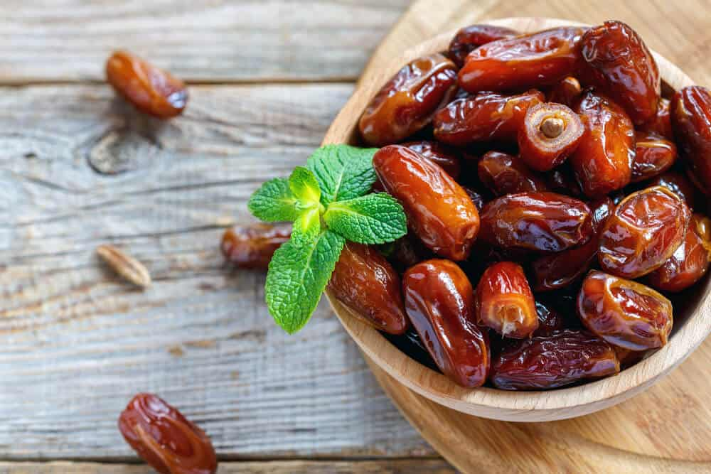 A bowl of dates with mint.