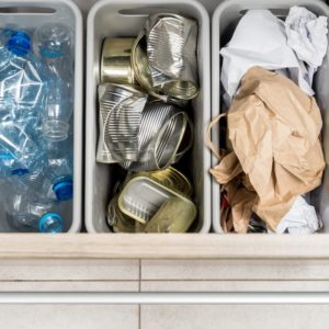 A close look at a garbage bin drawer with three receptacles for segregation.