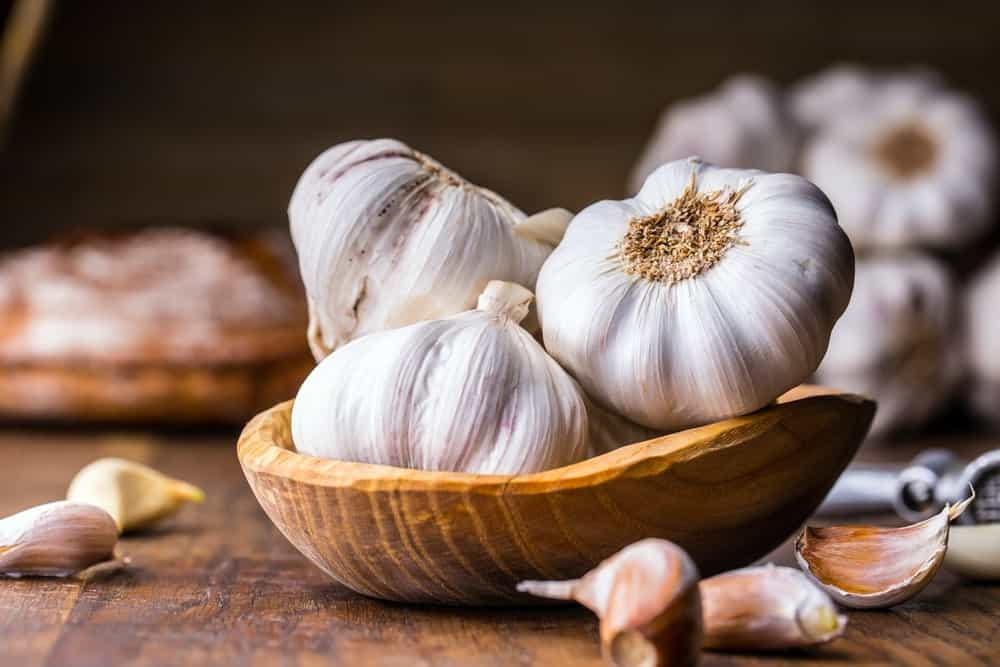 A bowl of garlic on a wooden table with cloves on the side.