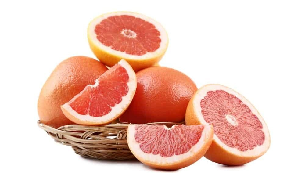 Slices of grapefruits along with two whole pieces in wicker bowl.