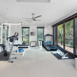 This is a fully equipped home gym with bright walls and ceiling.