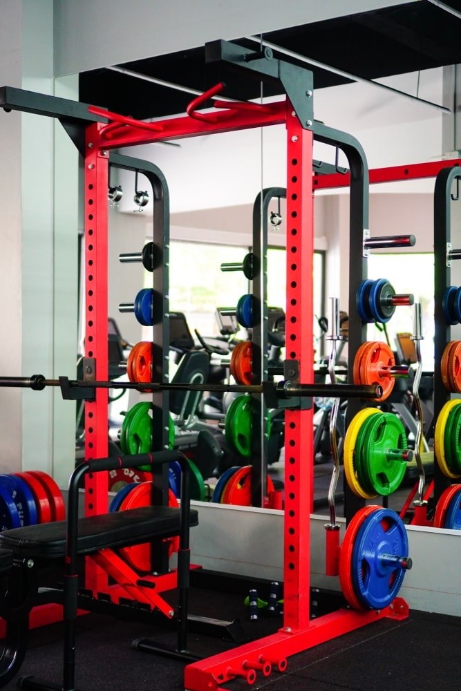 A bright red squat rack that has colorful plates.