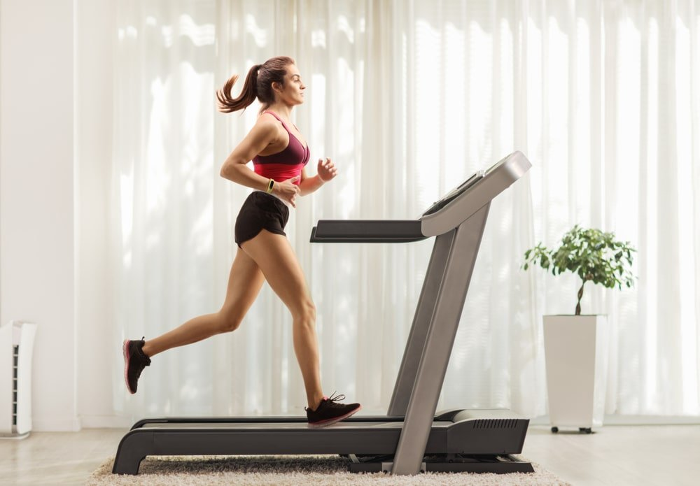 A woman exercising on the treadmill at home.