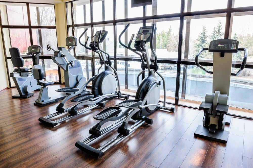This is a home gym with a couple of elliptical machines facing the glass wall.