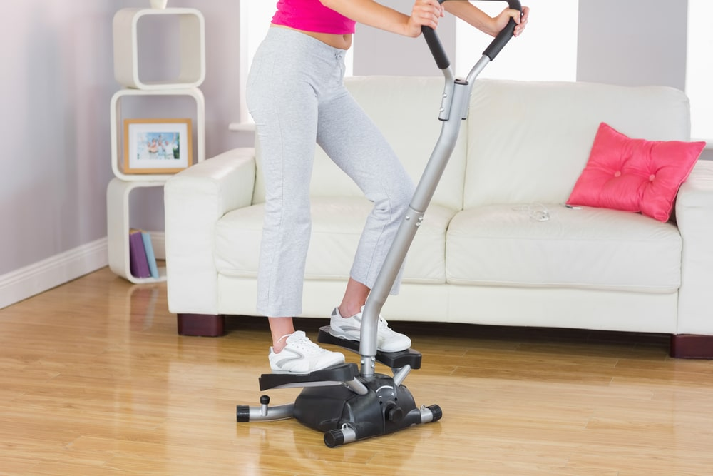 A woman exercising on a stair climber machine in the living room.