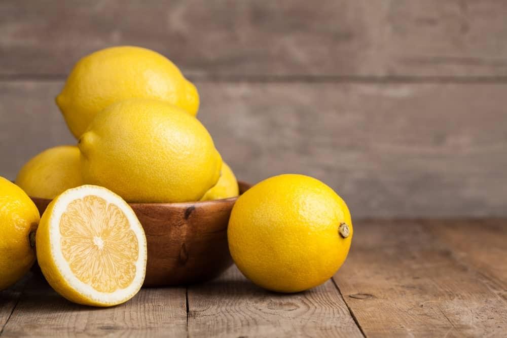 A bowl of lemons on a wood plank table.