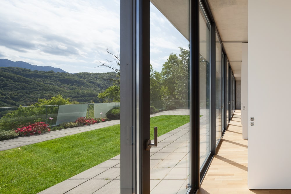 A look at a house corridor with glass walls and sliding glass doors.