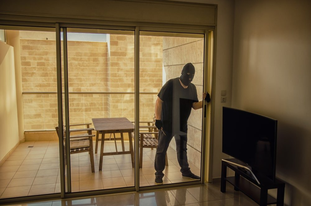 A thief breaking into a house through the sliding glass doors.