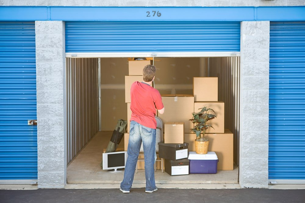 A man pulling down the door of his storage unit.