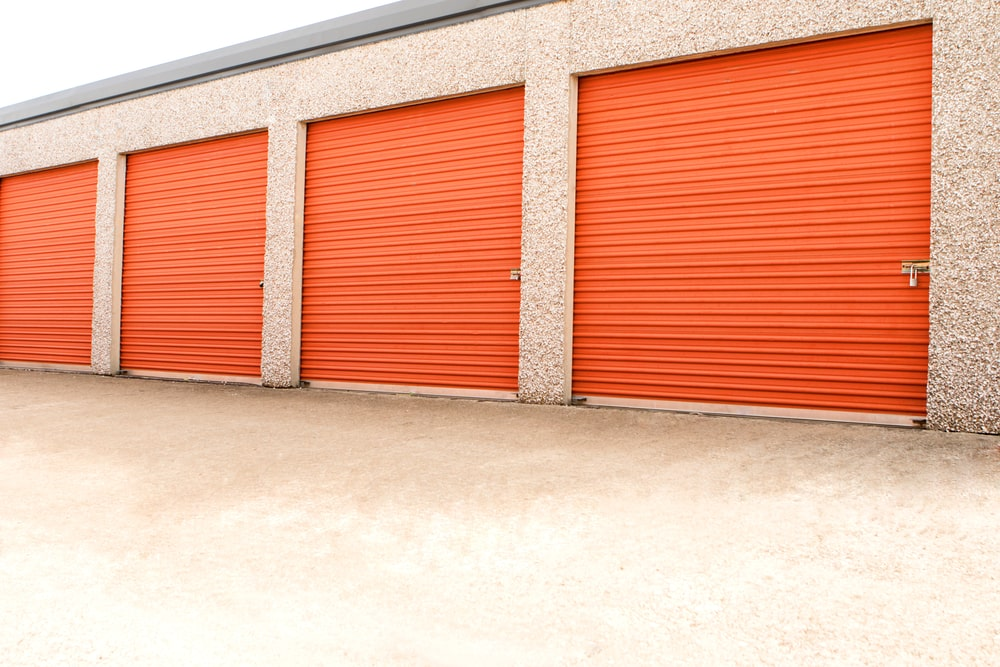 A row of bright orange storage units in a self-storage facility.