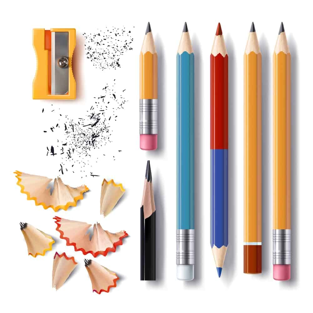 Various kinds of pencils in multi colors along with a sharpener and pencil shavings.