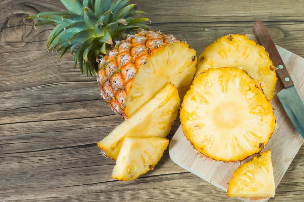 Sliced pineapples with a knife on a wooden chopping board.