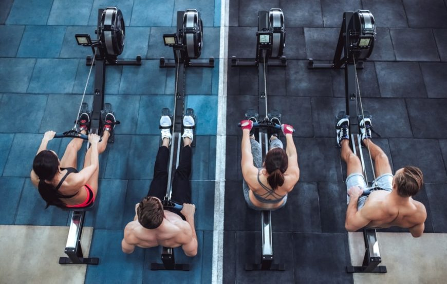A top view of two women and two men exercising on row machines.