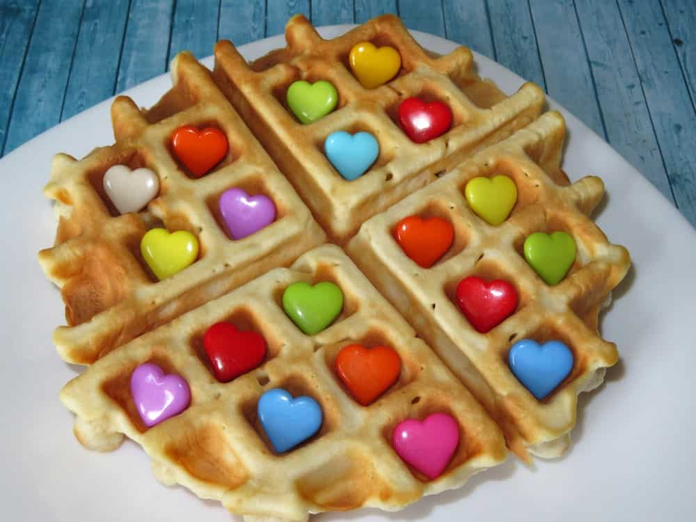 Waffle topped with colorful heart-shaped candies.