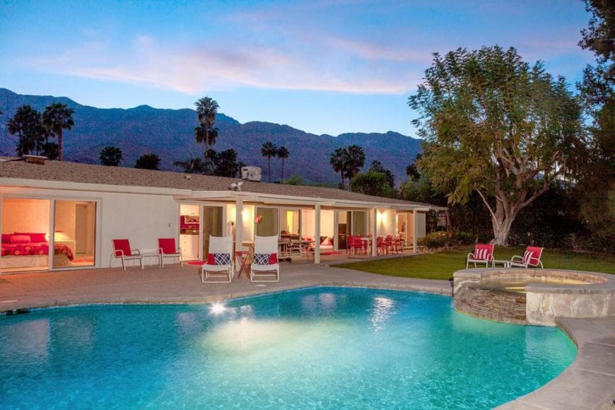 This is a look at the back of the house from the vantage of the poolside area. You can see here the glass walls of the house that glow warmly from the interior lights. Image courtesy of Toptenrealestatedeals.com.