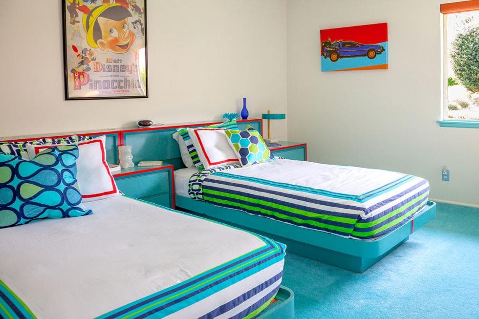 This bedroom has a couple of colorful beds that blend well with the carpeted flooring and the wooden headboard structure. Image courtesy of Toptenrealestatedeals.com.