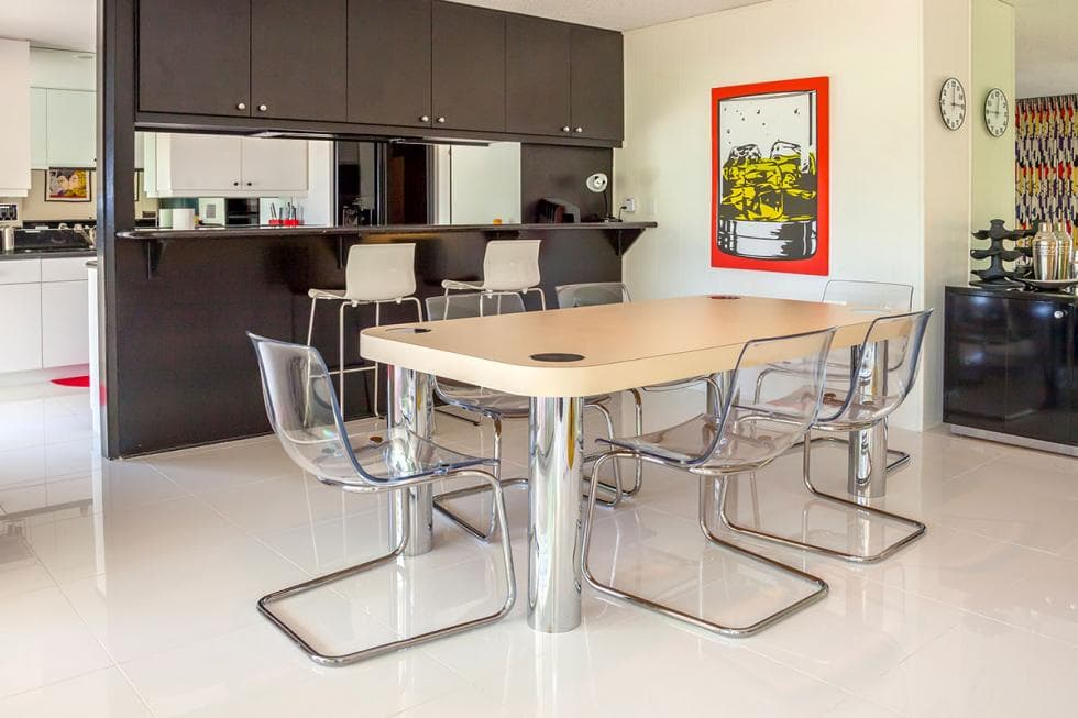 This is the dining area with a wood-top dining tables that has stainless steel legs to match the surrounding modern chairs. Next to it is a breakfast bar with dark brown tones. Image courtesy of Toptenrealestatedeals.com.