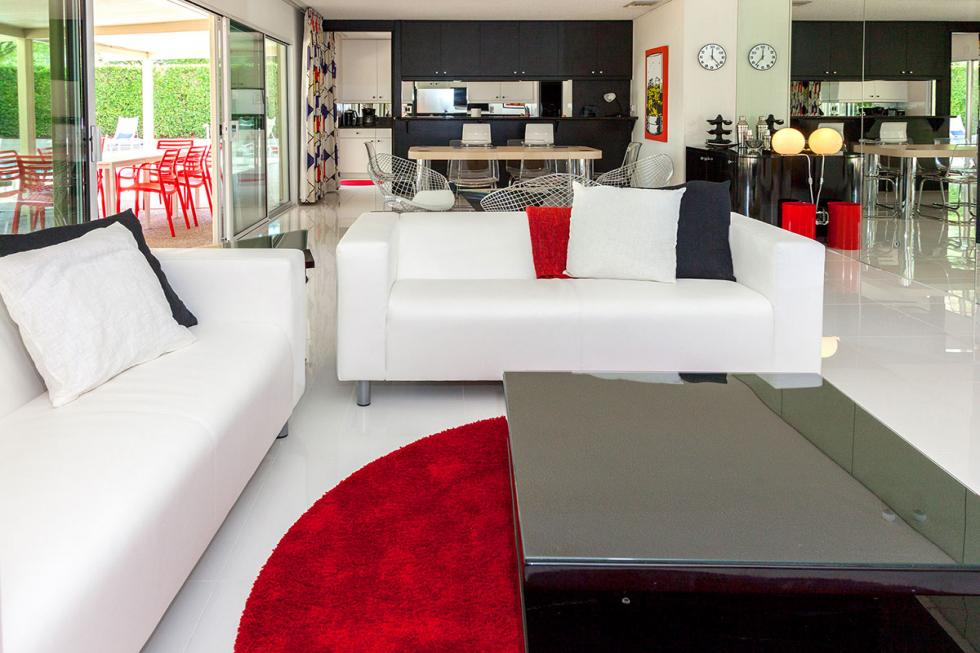 This is a close look at the living room with a couple of white sofas and a black coffee table. These are then complemented by the red accents. Image courtesy of Toptenrealestatedeals.com.