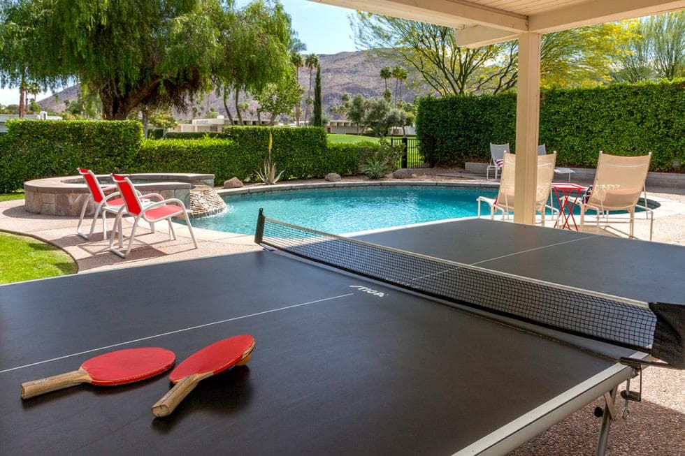 This is the covered patio a few steps from the poolside area. This area is fitted with a ping pong table with a dark tone to contrast the beige exteriors of the house. Image courtesy of Toptenrealestatedeals.com.