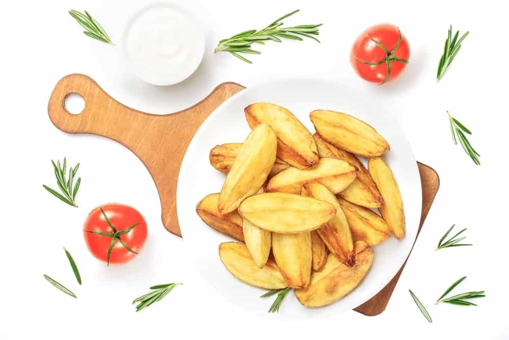 Wedge cut fries served on a white plate.