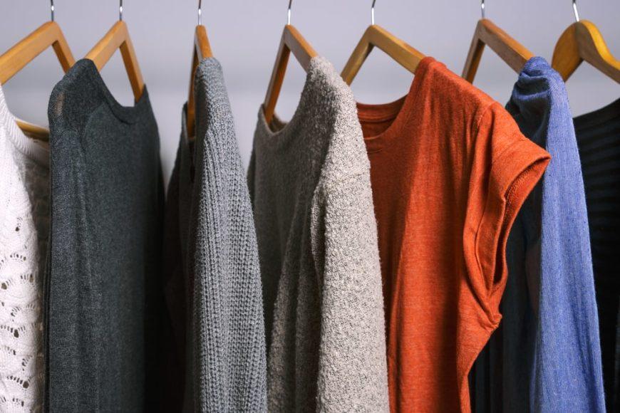 Various clothes hanging on a closet rack.