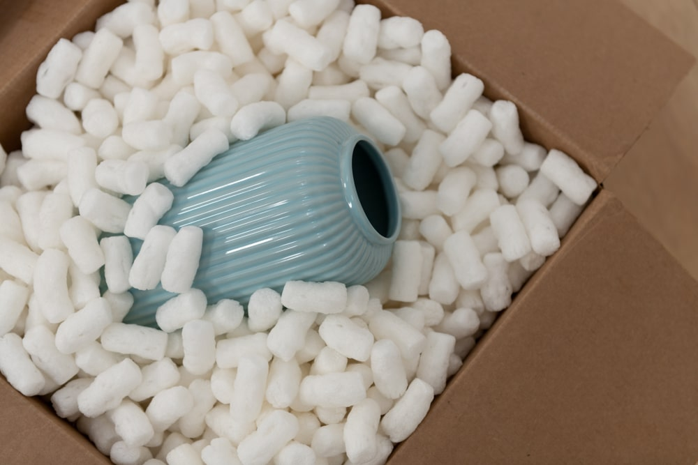 A vase in a box protected by foam packing peanuts.
