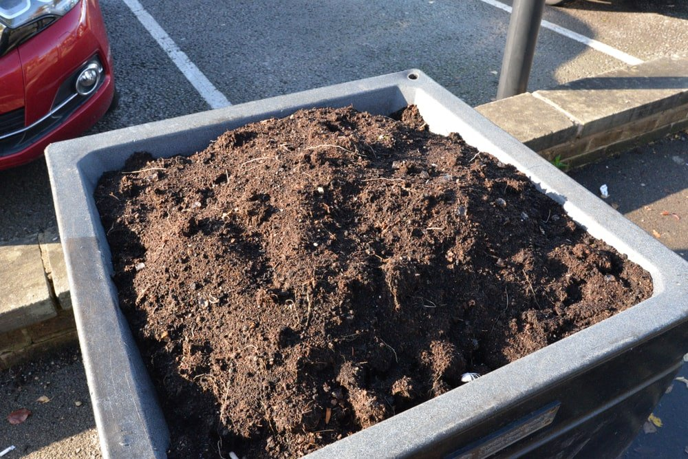 A large square planter filled with compost soil.