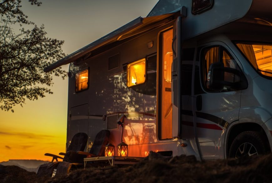 This is an RV that is parked at a camping ground during sunset.