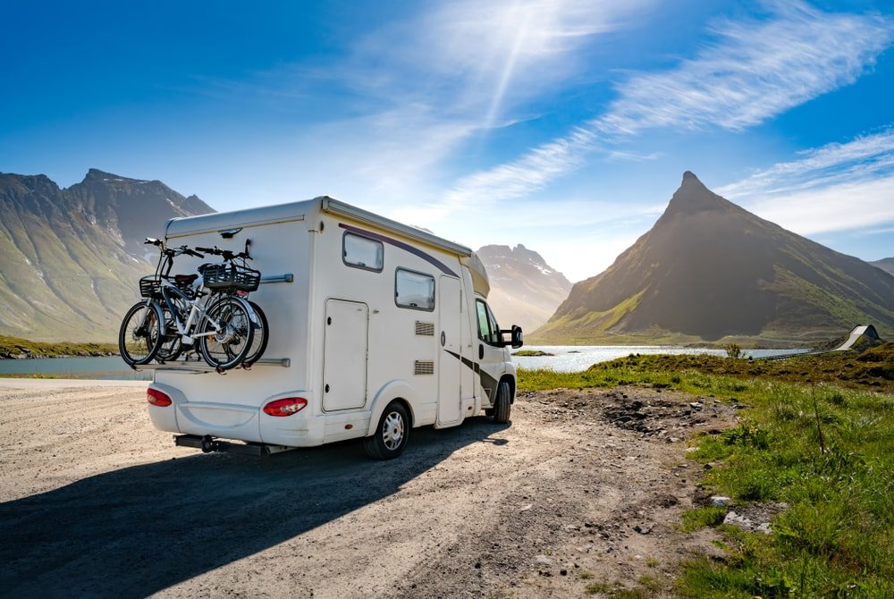 A large white RV at a camping ground with a beautiful Norway scenery.