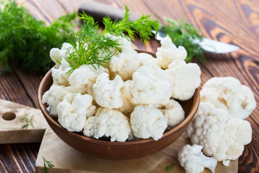 A bowl of white cauliflower on a wood plank table.