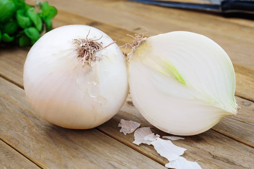 White onions on a wood plank table.