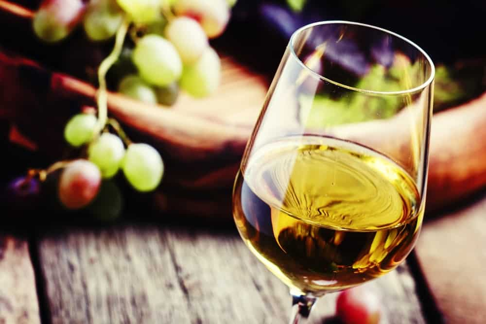 A glass of white wine against blurred grapes and wooden backdrop.