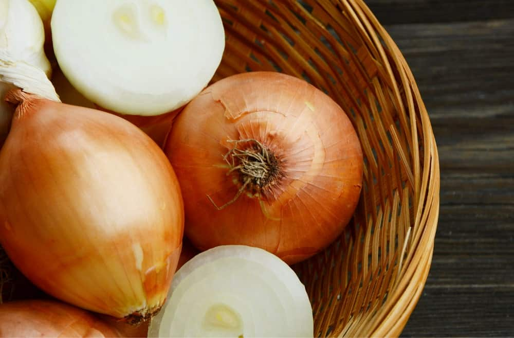 White onions in a rattan container.
