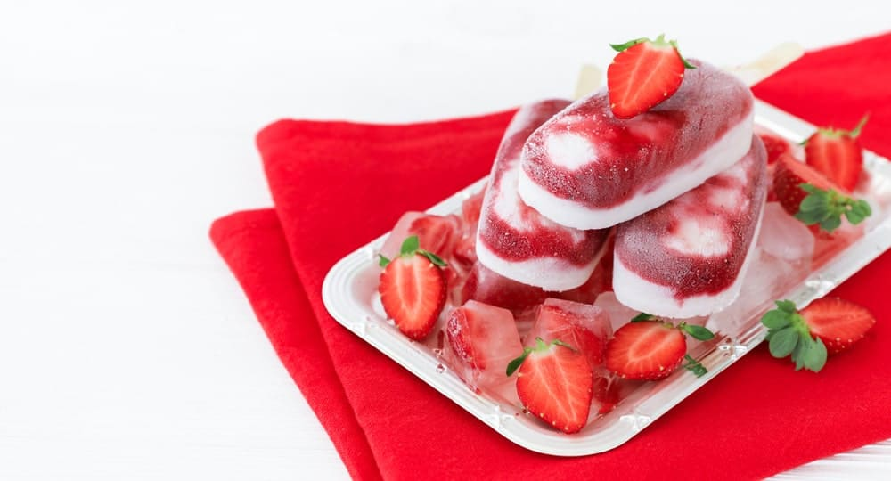 Yogurt parfait popsicles with strawberries on the side.